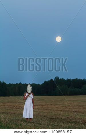 Scaring young woman wearing white dress with horse skull on her head at night field