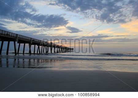 Gorgeous sunrise on the water with fishing pier