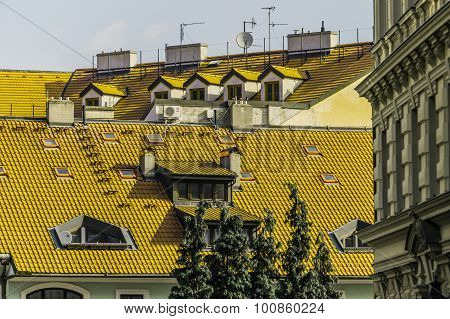 chimneys pipes antennas aerials satellite recievers on tiled bright yellow roofs