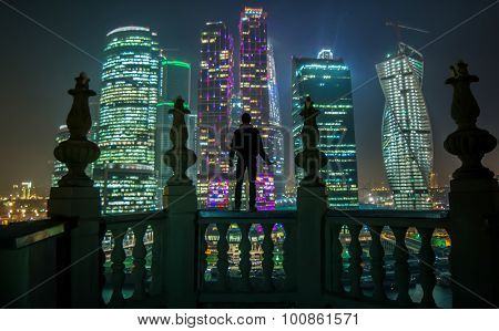 MOSCOW - OCT 30, 2014: Man stands on balcony and looks at Moscow International Business Center at dark night. Years of construction of complex - 1995-2018