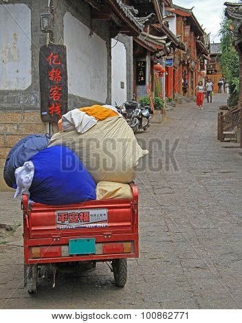 motor tricycle with sacks on the street in Lijiang