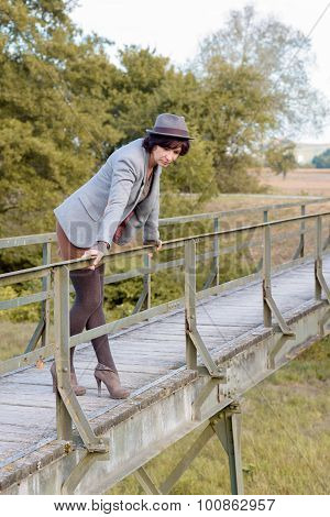 Fashionable Young Woman On A Rustic Footbridge