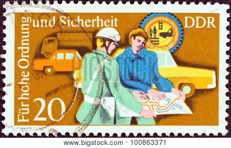 GERMAN DEMOCRATIC REPUBLIC - CIRCA 1975: Stamp shows Policeman assisting motorist