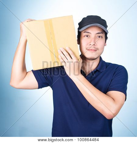Smiling Handsome Asian Delivery Man Giving And Carrying Parcel On Blue Background