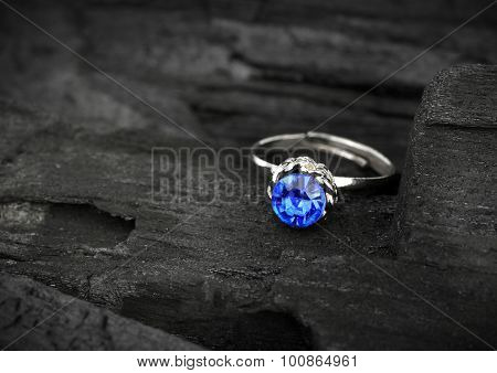 Jewellery Ring Witht Big Blue Sapphir On Dark Coal Background, Soft Focus