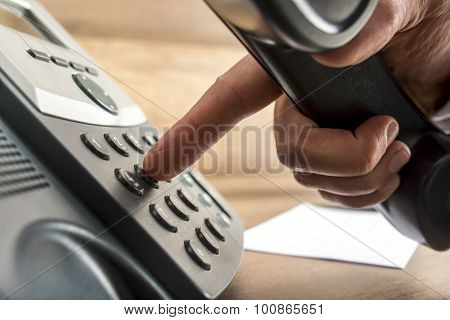 Closeup Of Male Hand Dialing A Telephone Number On Black Landline Phone