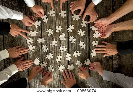 Businessmen Hands Holding Puzzle Pieces On Table
