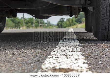 White Line On Asphalt Road Close Up Under Car