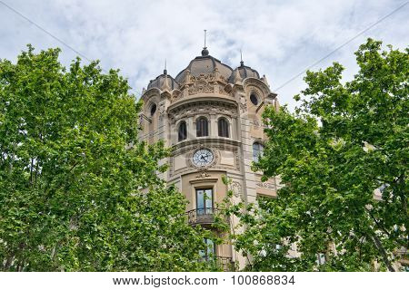 BARCELONA, SPAIN - MAY 02: Low Angle View of Old Domed Building with Clock Face Framed by Green Tree Tops in Barcelona, Spain. May 02, 2015.