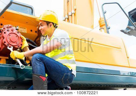 Asian engine mechanic engineer doing maintenance on machine