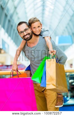 Dad carrying son piggyback in shopping mall
