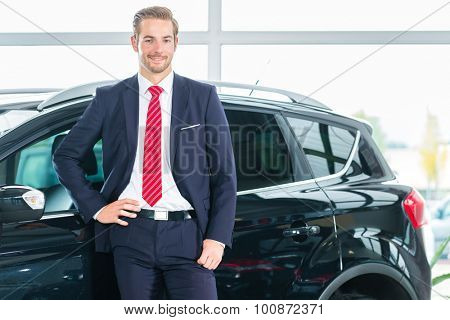 Seller or car salesman in car dealership presenting his new and used cars in the showroom