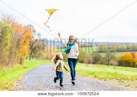 Girls fly an kite on autumn or fall meadow