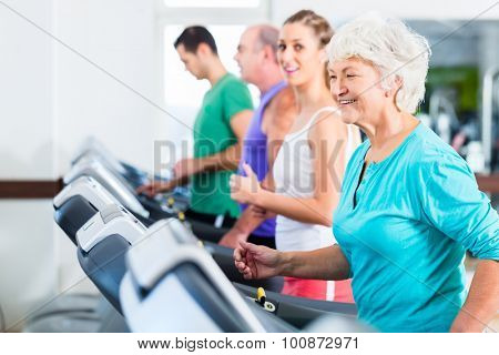 Group with senior and young men and women on treadmill in fitness gym running for sport