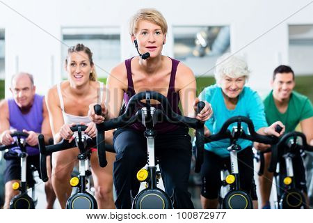Senior and young people spinning on fitness bike in gym doing endurance and cardio training, the instructor is leading them on