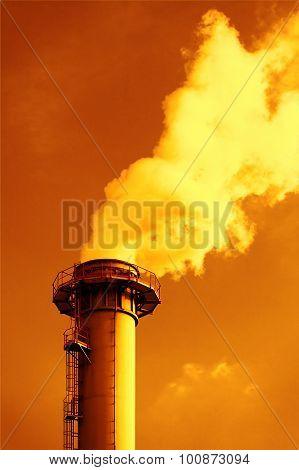Dense smoke from a chimney, sunset sky