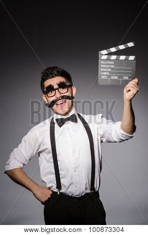 Young caucasian man with false moustache and clapperboard against gray
