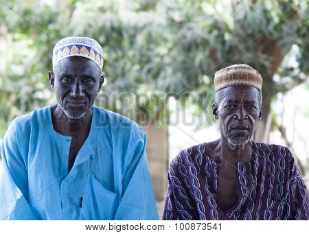 African village elders in traditional colorful clothes and muslim caps