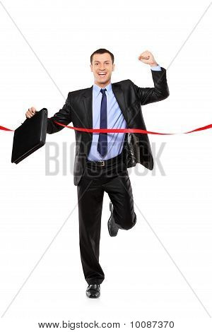 Full Length Portrait Of A Businessman Running At The Finish Line