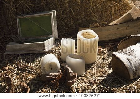 candles, firewood and wooden box lying on straw