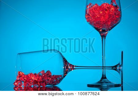 ice and empty wineglasses on color background