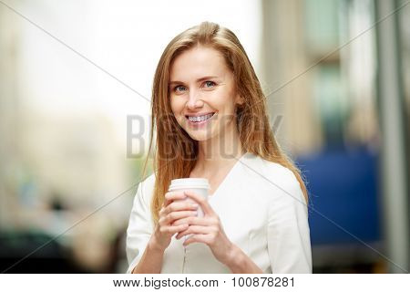 Young woman with coffe-to-go in street. Defocused background.