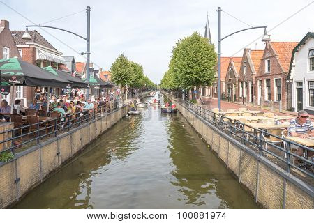 People on a terrace in the center of Balk along the canal The Luts.
