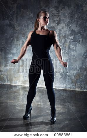 Strong woman bodybuilder in black clothing standing on wall background.
