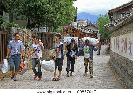 men are carrying sacks in Lijiang