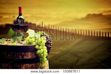 Red wine bottle and wine glass on wodden barrel. Beautiful Tuscany background