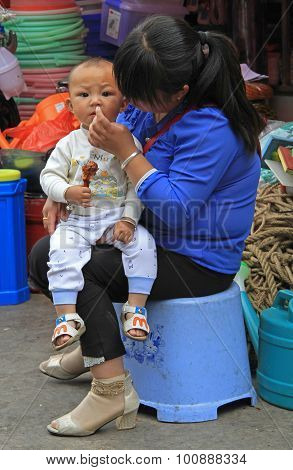 woman is wiping snuffles of her son in Lijiang, China
