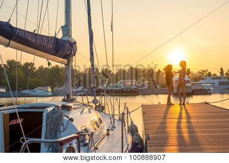 Two girls near the yacht at sunset.
