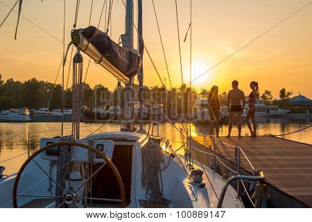 Young people near the sailing yacht.