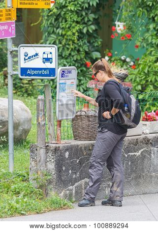 Lenk, Switzerland - July 23, 2015: Young Woman Checking The Timetable At The Bus Stop In Lenk, Switz