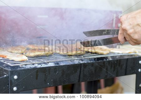 Man Preparing Smoky Barbecue On The Grill