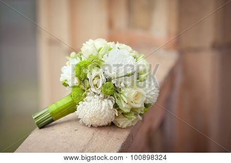 White and green bouquet on a stone parapet