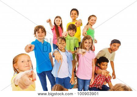 Large group of cute kids pointing at camera