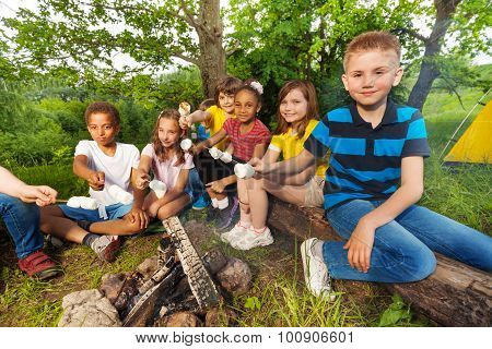 Group of kids sit near bonfire with marshmallow