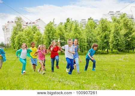 Running boy with airplane toy and children behind