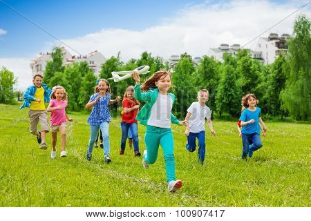 Running girl holding airplane toy and kids behind