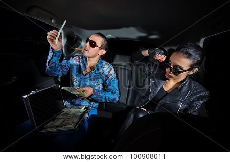Two gangsters with dollars in the car