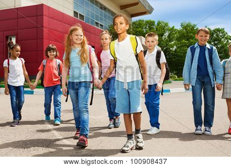 Children holding hands carry rucksacks and walk