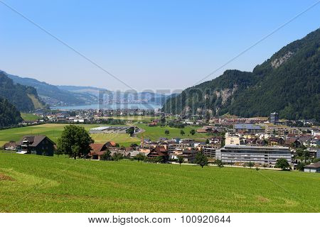 Scenic Alps Pastures, Town, Lake And Mountains