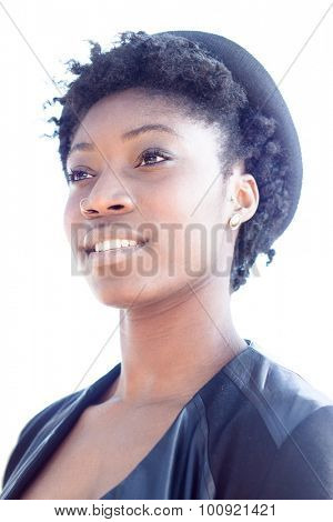 Low angle head and shoulders portrait of a fashionable stylish young African woman with a dreamy look wearing a trendy black outfit with hat, isolated on white