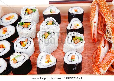 California Roll with Avocado and Salmon, Cream Cheese and Raw Salmon inside. on wooden plate with live crab  . isolated over white background . Maki Sushi and Sashimi