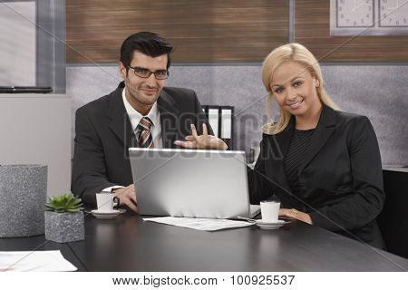 Happy businesspeople sitting at table, working together, using laptop computer, looking at camera.