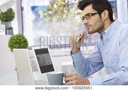 Young businessman sitting at desk, thinking, using laptop computer and tablet.