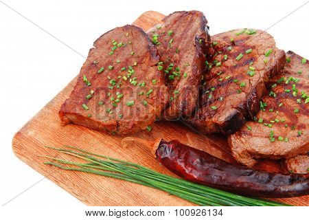 fresh ripe roasted beef meat on wooden plate with thyme and chives isolated on white background