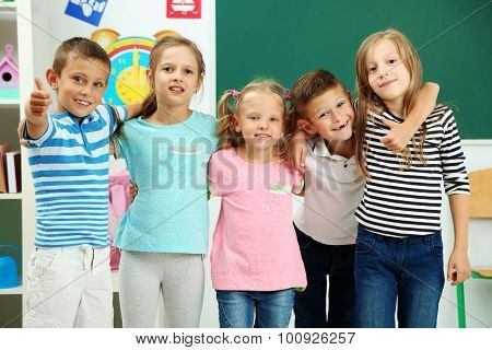 Portrait of happy classmates looking at camera in classroom