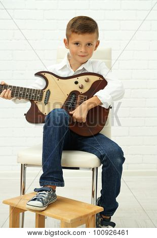 Little boy playing guitar on light background